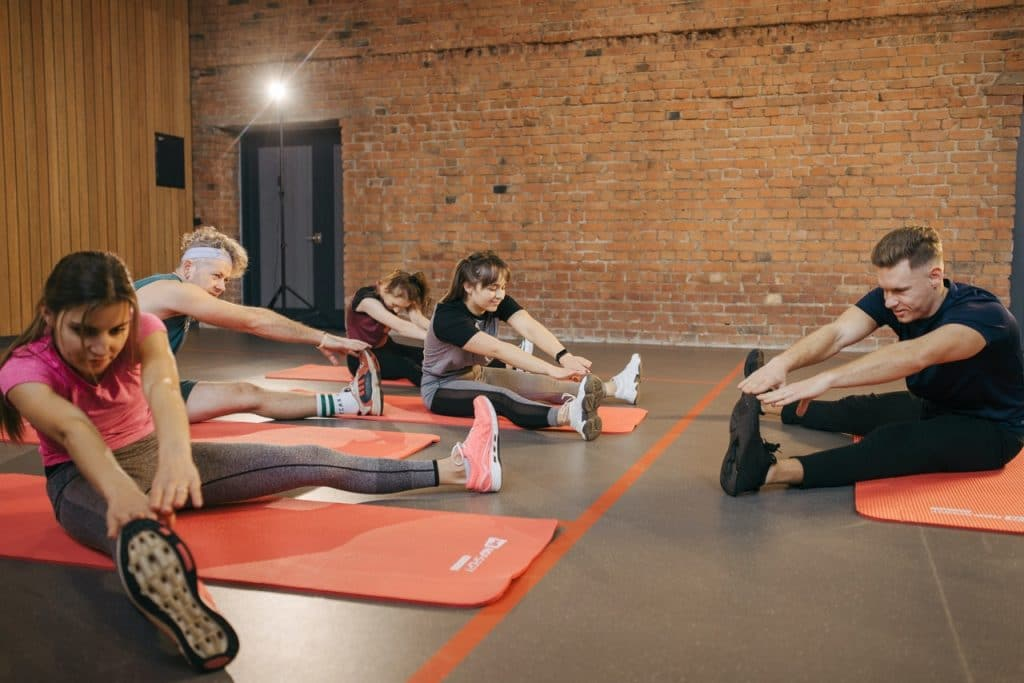 Group of people doing exercises in the gym.