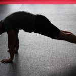 a man standing in a bad posture while doing push-ups
