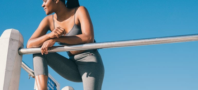 A woman is wearing grey leggins and standing on a fence.