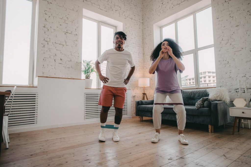 Two people working out with resistance band.