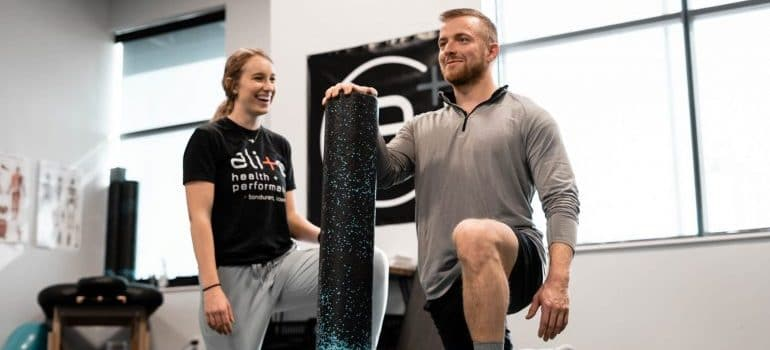 man exercising his knees with a trainer