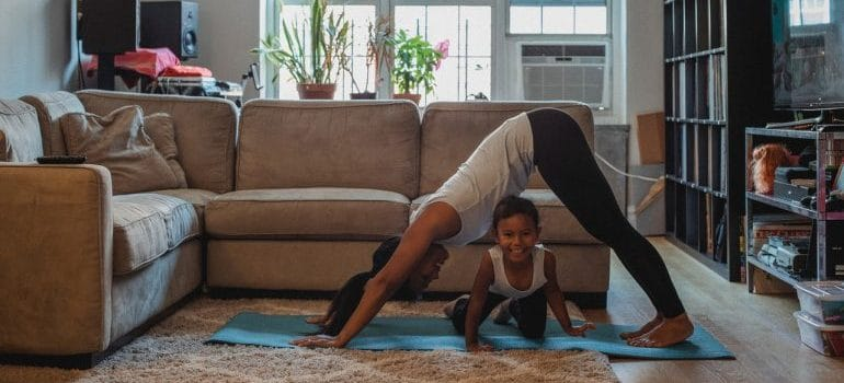A woman exercising with her child.