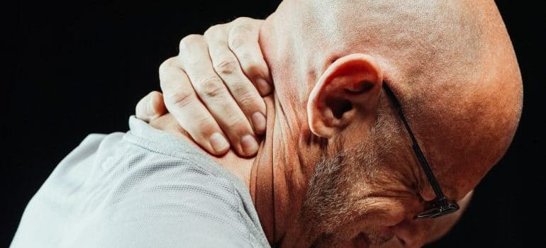 Person holding his neck due to neck pain
